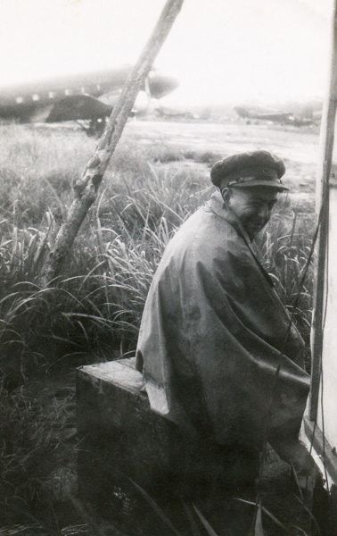 War Correspondnet Jack Hickson taking shelter from the rain at H