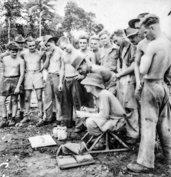 Ground crews on a Morotai airstrip gather around W.E. Pidgeon (W